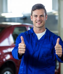 Portrait of smiling mechanic standing in repair shop showing thumbs up