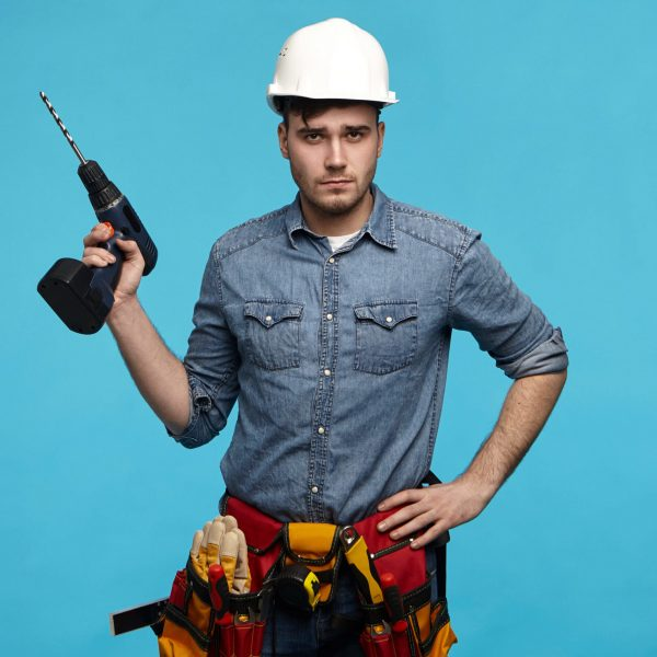 People, repair, equipment and renovation concept. Stylish young Caucasian repairman wearing hardhat, tool belt and overalls going to hang picture on wall, posing in studio with drill in his hand