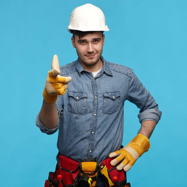Horizontal shot of handsome young maintenance service worker wearing white helmet, tool belt and gloves holding hand on his waist and pointing fore finger at camera, flirting with married housewife