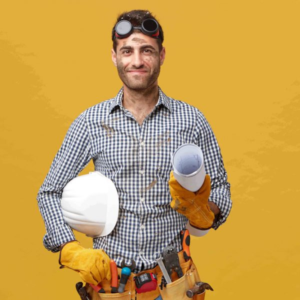 Pleased dirty man worker having prootective goggles on head and holding rolled paper with hardhat isolated over yellow background. Professional handsome male with belt of tools going to work
