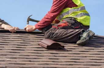 Concept of construction process. Two skilled roofer in special work wear with helmet in hands installing asphalt shingle or roof tile on top of new house