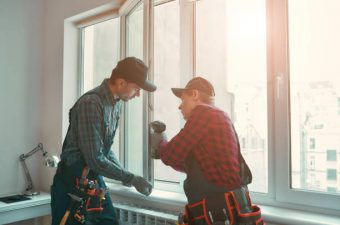 Portrait of mature men wearing uniform standing indoors and installing new windows in the apartment. Horizontal shot