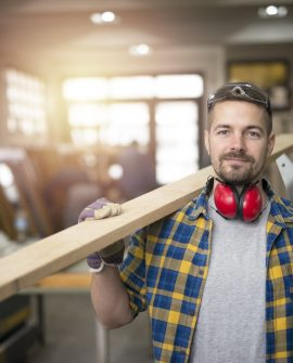 portrait-professional-middle-aged-carpenter-with-wood-plank-tools-standing-his-woodworking-workshop