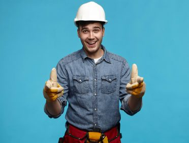 Horizontal shot of attractive young unshaven male builder wearing safety helmet, gloves and tool belt having excited look, gesturing emotionally, happy that his team finished construction works